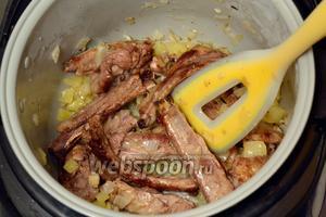 Добавляем мелко нарезанный лук, сладкий перец и чеснок, продолжаем обжаривать, пока овощи не станут мягкими, после чего программу «Жарка» выключаем.