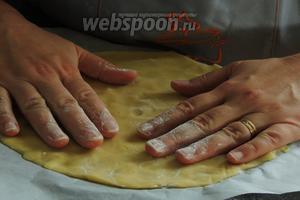 Тесто уже дозрело. Выкладываем половину теста прямо на пекарскую бумагу на дно разъёмной формы (у меня 26 см). И придавливаем руками, таким образом заполняя всё дно. Скалкой раскатать не получится, так как тесто будет постоянно липнуть, а если добавлять муки, то поменяется уже консистенция.