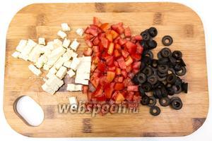 Поставим орзо вариться. Варим, как обычные макароны, в подсоленной воде, до готовности. Пока паста варится, помидоры и сыр Фета нарежем кубиками, оливки — кружочками.