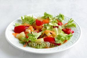 Салатные листья нарвать руками в тарелку, добавить морковь, ананас и помидоры.