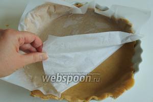 Вместе с бумагой поднимаем тесто и просто переворачиваем на форму. Смазывать форму ничем не надо, тесто и так достаточно жирное. Снимаем бумагу.