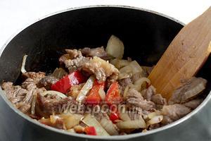 Всё мясо соединить в сотейнике, добавить лук и сладкий перец. Обжарить 5-7 минут.