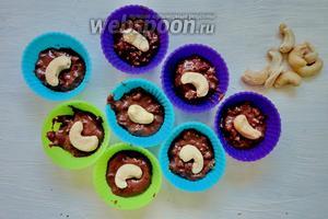 Формочки для конфет наполняем шоколадом на половину. Затем на середину укладываем по 1 орешку.