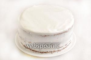 Обмазать торт белоснежными сливками со всех сторон. Можно дать ему немного охладиться в морозилке, минут 10.