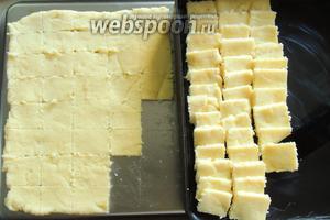 Как только слой каши станет достаточно упругим, нарезаем ножом на квадратики, размером около 5х5 см. Ножик постоянно ополаскиваем в холодной воде. Затем квадратики манки переносим на смазанный маслом, другой противень или форму. Выкладываем квадратики черепицей.