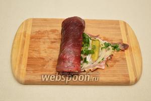 Аккуратно и плотно завернуть мясной пласт с начинкой в рулет.