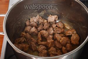 В кастрюле с толстым дном нагреть масло и обжарить мясо, приправив его солью и перцем.