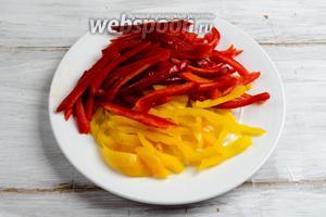 Тем временем подготовить овощи: лук очистить и нарезать полукольцами, а перцы — соломкой.