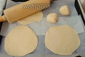 Раскатаем скалкой кусочки теста в круги, толщиной около 3 мм, на припылённом мукой рабочем месте. Затем переносим тесто на выстланный пекарской бумагой противень.