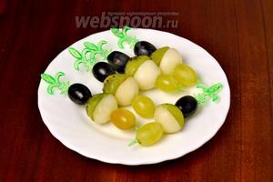 Формируем канапе: нанизываем на шпажки тёмный виноград, киви, грушу (плоскими сторонами друг к другу), светлый виноград.