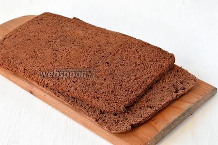 Провести ножом вдоль формы. Опрокинуть шоколадный бисквит на разделочную доску. Пергаментную бумагу снять, а корж разрезать на 2 горизонтальных пласта.
