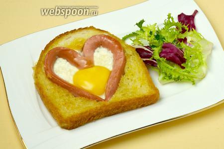 Подаём яичницу, выложив на тарелку и, по желанию, дополнив зелёным салатом, свежими овощами, соусом и так далее.
