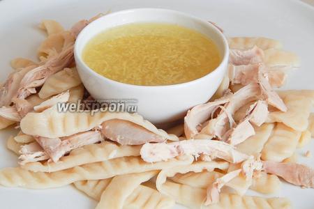 Остаётся лишь собрать кушанье. На большое блюдо в середину ставим пиалу с соусом, а вокруг укладываем горячие галушки с куриным мясом. Посыпаем измельченный зеленым луком. Подаем с картофельным бульоном. Ну очень вкусно, сытно и аппетитно.