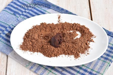 Набирать шоколадную массу чайной ложкой и выкладывать в тарелку с какао. Формировать трюфели, обкатывая их в какао.