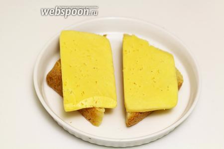 Возьмём подходящую жаропрочную форму, выкладываем хлебушек. На каждый ломтик хлеба добавляем по пластинке твёрдого сыра. Отправляем на гриль до расплавления сыра. Этот процесс происходит очень быстро, так что следите, чтобы сыр не сгорел.