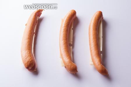 Вкладываем полоску сыра внутрь каждой сосиски, соединяем половинки.