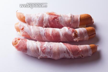 Как видите, бекон почти полностью обхватывает сосиски, он удерживает их, чтобы не разваливались при жарке и чтобы не выливался сыр.