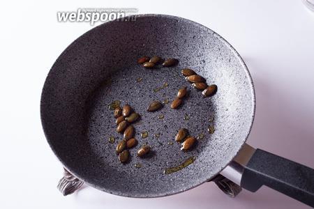 Обжариваем тыквенные семечки в растительном масле. Не в тыквенном — оно очень густое и тёмное, семечки в нём приобретут подгорелый вид.