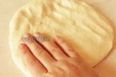Сначала обмазать стол маслом. Делаем это прямо руками, для работы нужны будут также масляные руки. Если налить на стол чересчур много масла, то тесто будет трудно раскатывать, оно не будет слушаться. Берём подошедшее тесто и разминаем его масляной ладошкой по всему кругу, как бы раскатывая его.