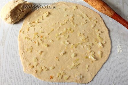 Тесто сначала разделите на 2 половины. Затем раскатайте каждую часть теста толщиной 2 мм, подпыляя стол мукой. Смажьте обжаренным луком.