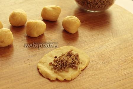 Тесто делим на небольшие шарики, размером с крупную сливу. Каждый шарик обминаем руками в лепёшку. Кладём фарш и скрепляем концы, формируя пирожки.