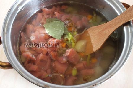 В кастрюлю выложите поджарку из овощей, добавьте кусочки лосося, влейте вино и воду. Добавьте соль, лавровый лист и перец.