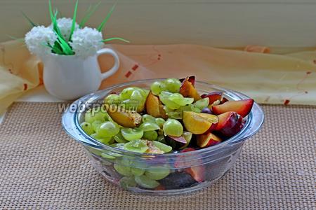 Пока выпекается основа, приготовим фрукты. Сливу нарезать на дольки, косточки удалить. Крупные виноградины тоже разрезать пополам.