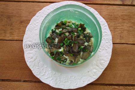 На слой рыбы выложите обжаренные грибы. Слой грибов полейте немного майонезом.