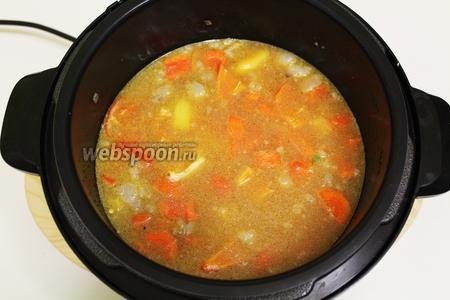 Наливаем овощной бульон, который можно заменить водой. Закрываем крышку. Включаем режим «суп» на 12 минут.