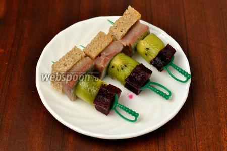 Нанизываем на шпажки подготовленные ингредиенты в следующем порядке: свёкла, киви, сельдь, хлеб.