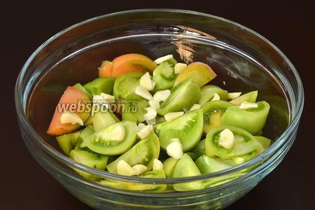 Пока готовится маринад, помидоры помыть, порезать на дольки. Добавить почищенный и порезанный крупными пластинками чеснок.