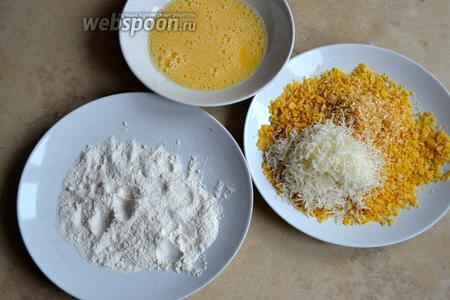 Подготовить 3 блюда. В 1 насыпать муку, во 2 разбить 2 яйца и размешать вилкой, в 3 блюдо насыпать измельчённые кукурузные хлопья, добавить тёртый сыр, луковые хлопья и соль по вкусу. Как следует перемешать эту сухую смесь.