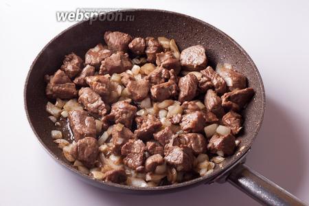Добавляем к баранине лук и чеснок и жарим их вместе на среднем огне 2-3 минуты, периодически помешивая.