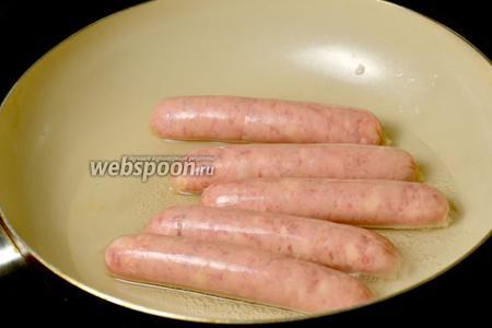 Колбаски слегка провариваем в небольшом количестве воды, поворачивая их на сковороде.