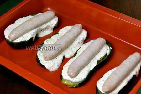 В форму для запекания кладём 4 половинки баклажанов, намазываем их соусом, сверху кладём колбаски.