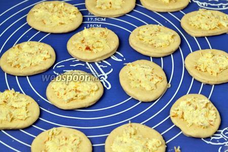 На каждый кружок кладём сырную начинку и распределяем её по тесту.