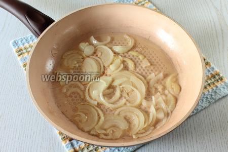 Репчатый лук нарежьте полукольцами и обжарьте на растительном масле до золотистого цвета.