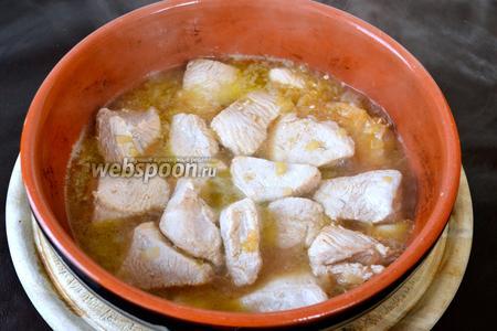 Когда мясо подрумянится, переложить его в глубокую тарелку и сохранять в тепле, в сковороду выложить мелко нарезанный лук и 1 целый зубчик чеснока. Обжаривать 3-5 минут. Затем вернуть индейку в сковороду с луком. Добавить белое вино. Накрыть сковороду крышкой, уменьшить огонь и тушить всё 30 минут.