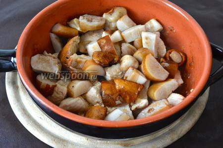 Тем временем порезать грибы (можно использовать шампиньоны). Через 30 минут добавить к мясу грибы. Осторожно всё перемешать.