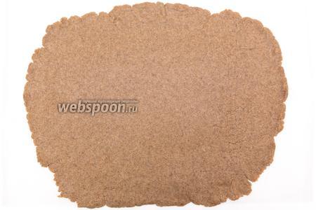 Тесто вынимаем из миски. Выкладываем на пергамент. Раскатываем в пласт толщиной 0,5-0,8 см. Я раскатала потоньше. Мне нравится, чтобы тесто не особо ощущалось внутри.