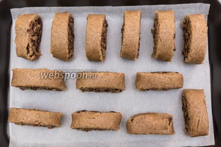 Выкладываем на противень, застеленный пергаментом, стоя. Выпекаем в разогретой до 200°С духовке 20-30 минут. Затем вынимаем противень, кладём печенье на бок и печём с каждой стороны ещё по 5-10 минут.