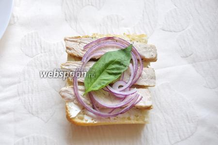 На творожный сыр выложите куски индейки, нарезанный на полукольца красный лук и положите листик базилика.
