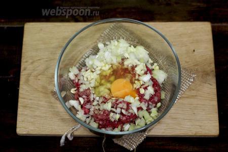 Приготовим котлетную массу. Лук и чеснок очищаем от шелухи, мелко нарезаем, добавляем к свиному фаршу. Разбиваем куриное яйцо, приправляем солью и молотым перцем. Хорошо перемешиваем.