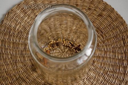 На дно чистой банки выложить пряности — горчицу в семенах, душистый перец, гвоздику, корицу.