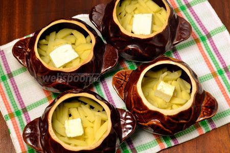 В горшочки сначала кладём картошку, в середину которой добавляем по кусочку сливочного масла.