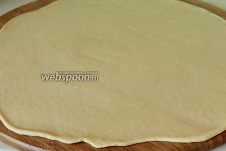 Раскатать тесто в токий круглый пласт. Раскатывайте как можно тоньше но и не подпыляйте стол слишком много мукой, тесто само жирное и поддатливое.
