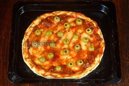 Оливки разрезаем на 2 половинки, раскладываем на пиццу.