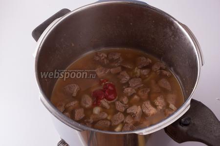 Лук томим с бараниной на слабом огне до прозрачности, тем временем кипятим 250 мл воды. Вливаем горячую воду, разбалтываем томатную пасту и варим на слабом огне 10 минут.