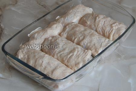 Выкладываем заготовки в подходящую форму и смазываем верх смесью сметаны с приправой, можно просто сметаной. Ставим запекаться на 40 минут при 180°С в духовку.