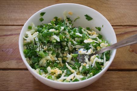 Куриные яйца отварить и очистить. Натереть на крупной тёрке. Добавить к зелени и перемешать. Можно добавить немного соли. Отставить.